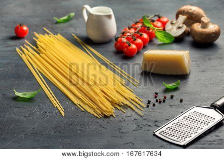 Raw Italian spaghetti with set of ingredients for cooking Italian pasta on dark stone surface