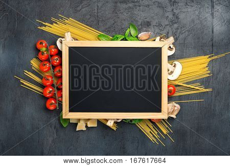 Small chalk board with copy space and ingredients for cooking Italian pasta on dark stone surface top view