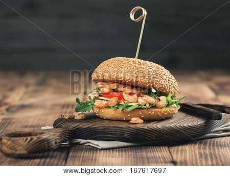Burger with grilled shrimp arugula tomato and cheese on wooden board close up with copy space