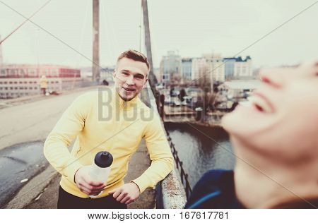 Couple athletes talking after a workout on a city bridge