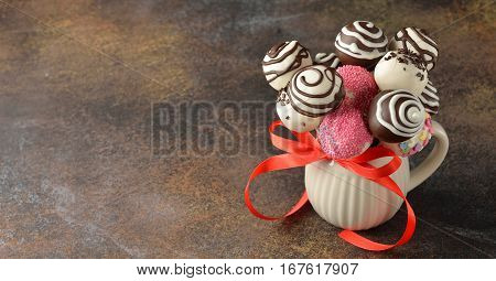 Cake pops decorated with white and dark chocolate on a brown background