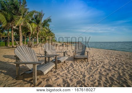 Wooden chair on a sunny beach. Tropical holiday