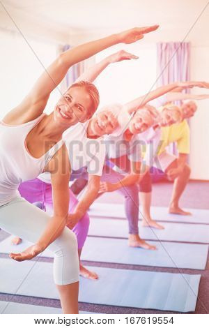 Portrait of instructor performing yoga with seniors during sports class