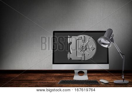Computer by table lamp against digitally generated grey background