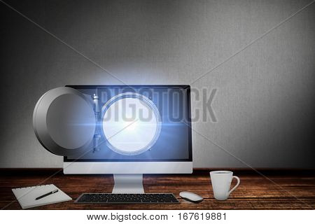 Computer by book and cup against digitally generated grey background
