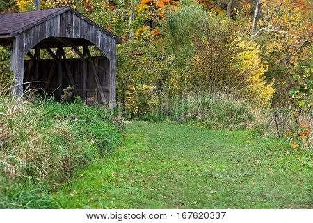 old wooden covered bridge in autumn trees
