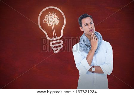 Handsome hipster looking away with hand on chin against image of a desk