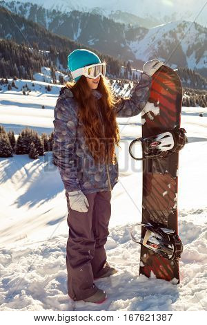 Girl Snowboarder Stands Mountain Top With Snowboard In Hands.