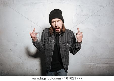 Portrait of a hipster man in hat showing fuck you sign and looking at camera isolated over wall background