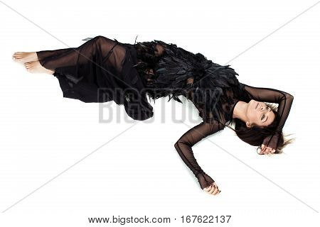 Nice womanlaying in studio on the floor and raising her hands with long black sleeves up and thinking. She is wearing nice long dark diaphanous dress with a lot of feathers
