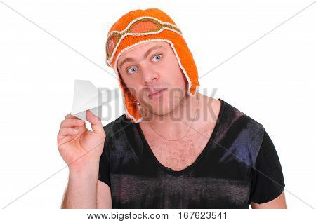 Adult male in a children's knitted hat pilot playing with a paper plane. The man let a paper airplane