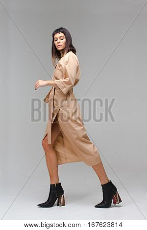 Young beautiful woman in studio shows that she is making steps. She has long light brown cloak and black boots. She is posing and playing role go away