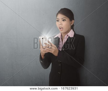Young Asian Business Woman Using Smartphone With Shocked Expression