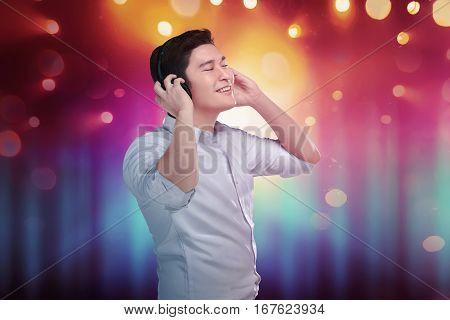 Cheerful Asian Man Enjoying His Favorite Music In Headphones