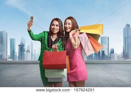 Portrait two asian woman with shopping bags taking selfie against cityscape background