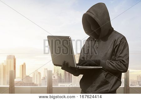 Hacker Man With Anonymous Mask Using Laptop To Hacking