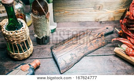 Wooden serving board on the table with wine bottles. Top angle view. Concept of vintage style winehouse or package store