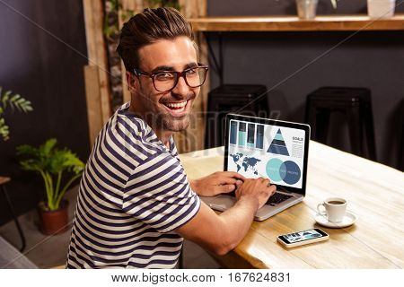 Digital composite image of business presentation with charts and map against happy man using laptop at cafe