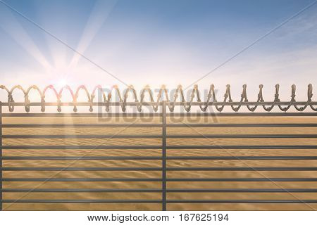 Digitallly generated image of barbed wire on fence against desert scene