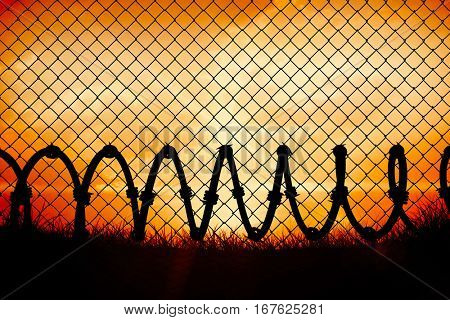 Chainlink fence against white background against orange sunrise