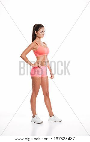 Full length side view of a young sexy fitness woman in pink sportswear isolated on the white background