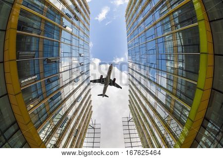 airplane flew above the modern glass buildings fisheye view