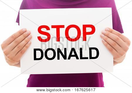 Girl holding white paper sheet with text STOP DONALD