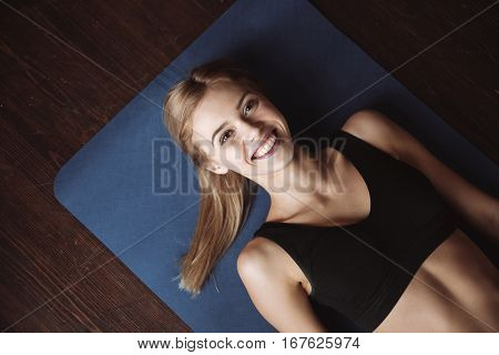 Top view of cheerful charming woman athlete lying on mat on the floor