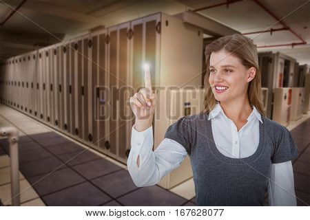 Smiling woman pointing something with her finger against data center