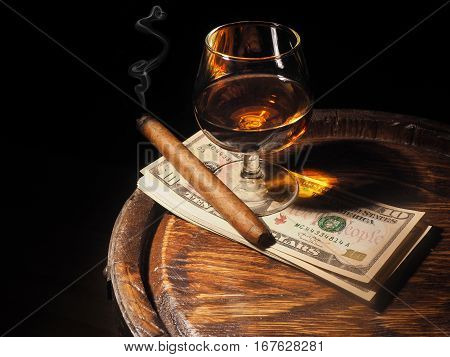 Cognac ,cigar And Dollars On Old Oak Barrel