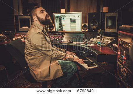 Sound engineer palaying on synthesizer in boutique recording studio.