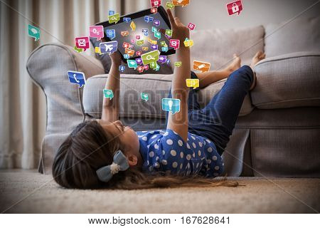 Little girl using digital tablet in the living room against colourful computer applications 3d