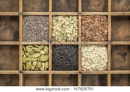 healthy seed collection (chia, hemp hearts, brown flax, pumpkin, black cumin, sesame) in a vintage wood typesetter drawer