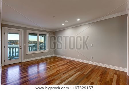 Empty Room With Hardwood Floor And Door To Balcony.