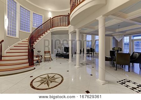 Stunning spacious entry foyer with columns boasts marble mosaic tile floor and grand staircase with glossy wood curved banister. The foyer flanked by formal dining room and living room. Northwest USA poster
