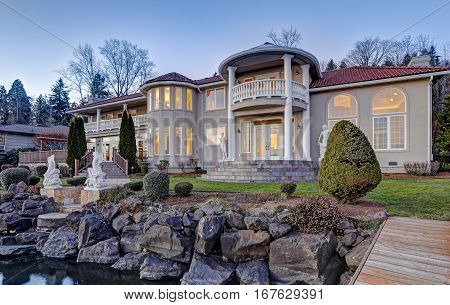 Luxurious Mediterranean style waterfront home exterior sunset view from the deck with rocky coast. Lake Washington. Northwest USA