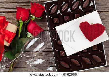 Valentines day greeting card. Red roses, chocolate sweets gift box and wine glasses on wooden table. Top view