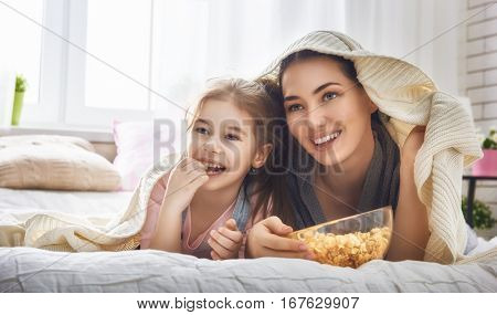 Happy loving family. Mother and her daughter child girl are eating popcorn on the bed in the room.