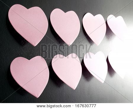 pink heart shaped sticky notes on dark brown wooden wall, communication on valentine's day concept