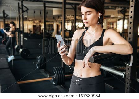 Beautiful young sportswoman listening to music with cell phone in gym