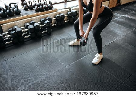 Closeup of woman athlete standing and working out with kettlebell in gym