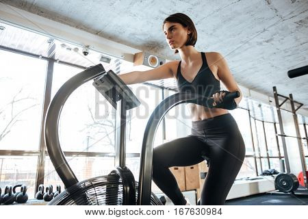 Serious young sportswoman exercising on bike in gym