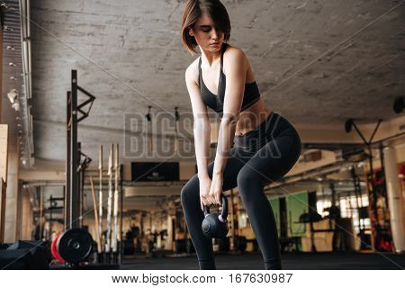 Attractive young sportswoman doing squats with kettlebell in gym