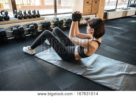 Slim young woman athlete working out with abdominal muscles in gym