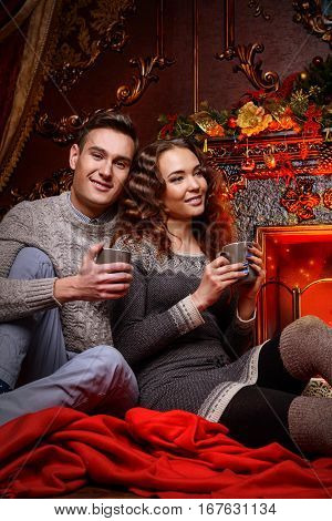 A loving couple sitting together in a cozy atmosphere by the fireplace. Love concept.