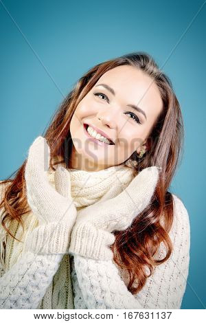 Winter and happiness concept. Pretty woman in white sweater, scarf and mittens smiling at camera. Good mood. Snowflakes.