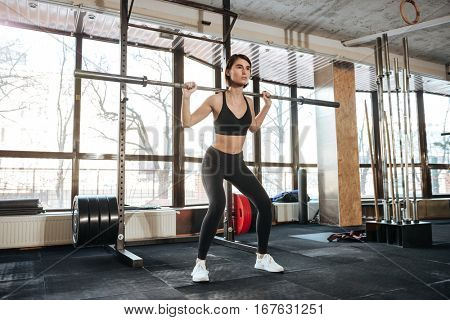 Attractive young sportswoman standing and working out in gym
