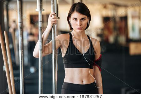 Attractive young fitness woman standing and listening to music in gym