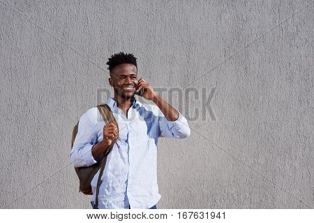 Handsome Man With Bag And Cellphone Standing By Wall