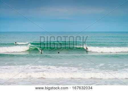 Adelaide Australia - August 14 2016: Surfers sliding the waves at Middleton Beach on a day. Middleton beach is one of the most famous places for surfing in South Australia